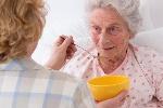 Carer-feeding-an-elderly-woman-750x500