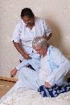 46443883-nurse-in-nursing-home-helping-elderly-man-getting-dressed