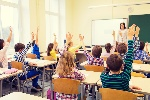 group-of-school-kids-with-teacher-sitting-in-classroom-and-raising-hands