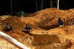 in-een-bos-in-het-noordwesten-van-liberia-werkt-een-groep-mannen-in-een-open-goudmij