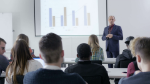 videoblocks-lecturer-presenting-charts-to-many-college-students-in-lecture-many-business-students-paying-attention-to-the-explanation-about-the-slides-in-the-modern-classroom_bbcoarqcx_thumbnail-full05