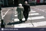 vista-posterior-de-una-pareja-de-ancianos-caminando-sobre-un-paso-de-peatones-con-el-hombre-ayudado-por-un-baston-y-la-mujer-ayudada-por-un-baston-blanco-para-invidentes-k92ywj