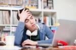 82212355-estudiante-masculino-preocupado-con-la-mano-en-el-pelo-usando-la-computadora-portátil