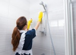 housekeeper-cleaning-shower-head-bathroom-reaching-up-to-wipe-as-sprays-detergent-rear-view-69400769