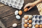 overhead-view-of-woman-holding-brown-egg-at-wooden-table-961606468-5c15c6d246e0fb0001951d86