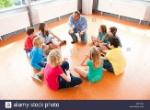 el-profesor-y-los-alumnos-haciendo-el-trabajo-del-proyecto-en-el-piso-de-un-aula-x8yyhc